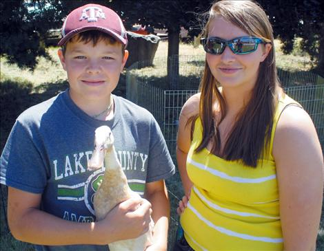 Monica poses with 4-H youth Phillip Vaughan and his project duck.