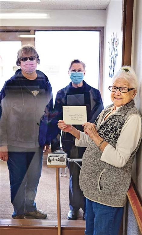 St. Luke Extended Care Resident Council  Chairperson Amelia Best presents three  $500 checks to local food banks with COVID-19  social-distancing guidelines used, in that a  glass partition was between her and the  organization representatives receiving the  donations.