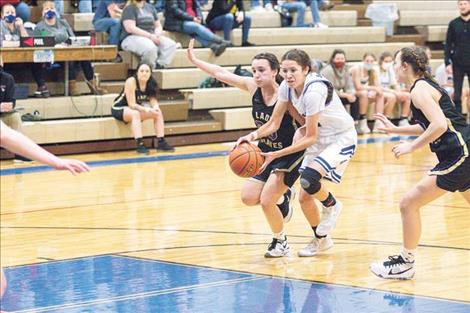 Mission Lady Bulldog Madyson Currie and Lady Pirate Julia Barnard fight for a loose ball.