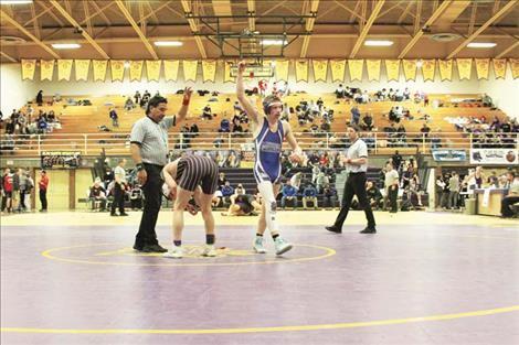 : Another victory for the Mission/Charlo Bulldogs. Below: Bulldog Charley Adams gains advantage.