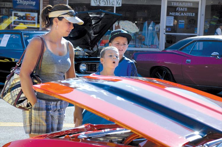 Niki, left, Cason and Colton Graham look at the flames painted on a shiny car at the Cruisen' by the Bay car show.