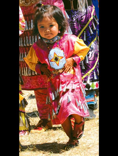 With her hands on her hips, a tiny jingle dancer dances in the Grand Entry.