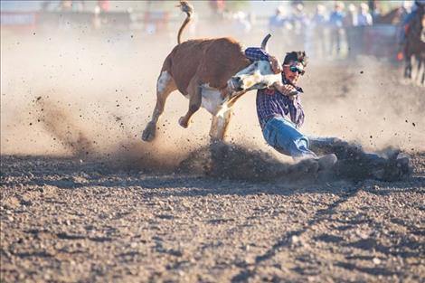 Tyler Houle, of Polson, battles his steer to the ground.