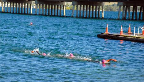 Three triathletes head for the docks at Riverside Park Saturday as they finish their 1.5 kilometer swim, only to head for their bicycles for round two.