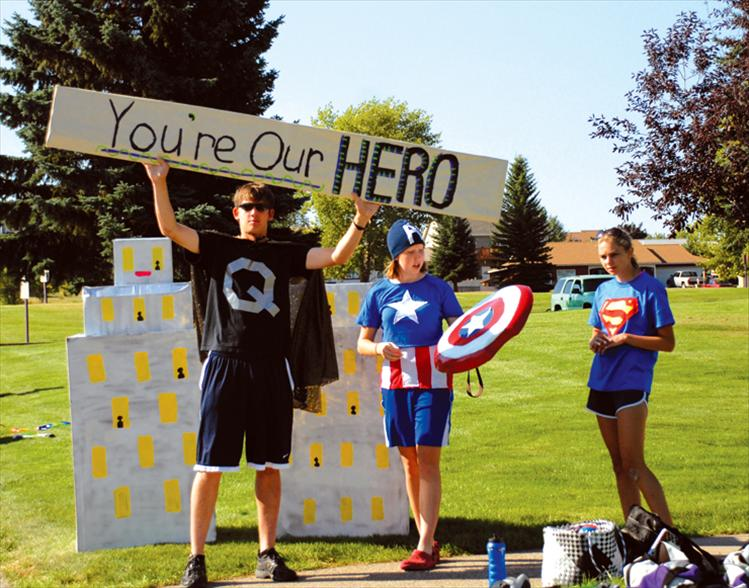 Quinn Harlan, left, Tegan Bauer and Amanda Stobie help man the Polson High School Cross Country Team aid station during the Polson Triathlon. Their theme was superheroes, and they had special cheers for their cross country coach Matt Seeley.
