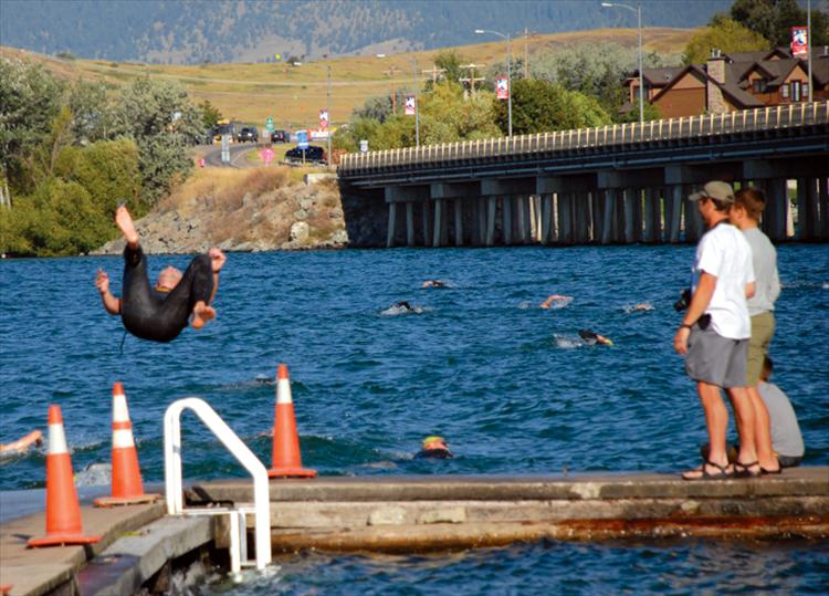 A somersault makes entry into the Flathead River more fun for a male triathlete as he begins the Polson Triathlon.