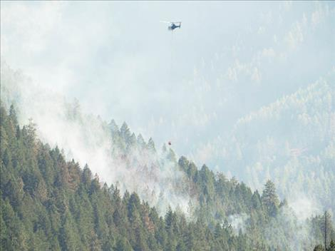 A helicopter prepares to make a bucket drop on a hot spot after refilling at Mission Reservoir on Sept. 3.