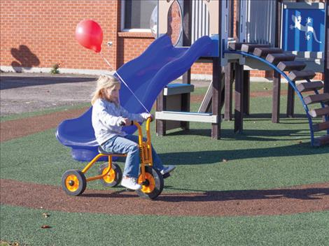 Winnie Hanson takes her red balloon for a tricycle ride along a path in the new playground.
