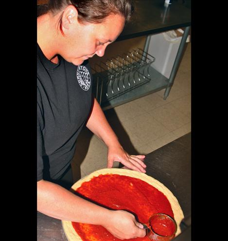 Rose Mansell, team leader,works over a sauce swirl on a pizza.
