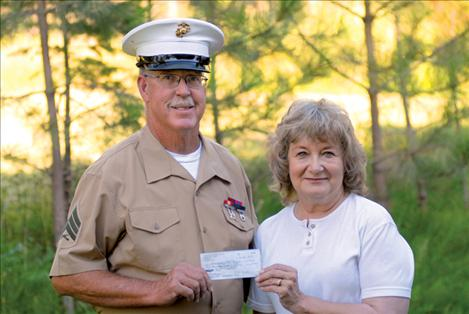 Chuck Lewis, representing Standing for the Fallen, donates funds collected at the Polson Flathead Cherry Festival to Magazines for Troops' Esther Gunlock.