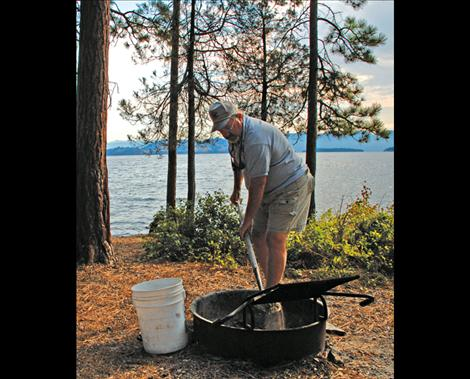 With the tools of his trade, a shovel and a bucket, Dave Gray cleans a firepit so the campsite will be ready for the next folks who come to enjoy the park.
