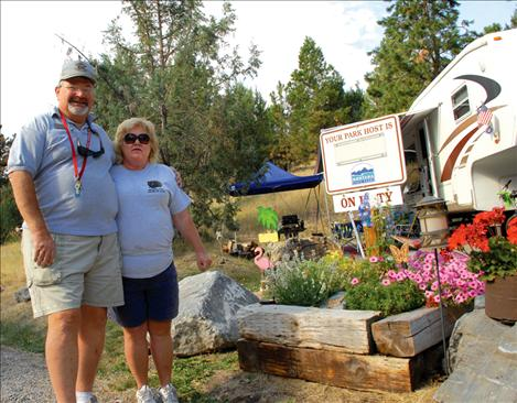 "Dave and Judy Gray plant flowers for ""a touch of home."" The couple hails from Haughton, La., and they spent the summer at Big Arm State Park as a camp host and volunteer."