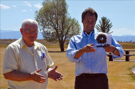 Governor Steve Bullock, right, is presented a pipe covered with quagga mussels at the Ronan checkpoint Friday by Rep. Mike Cuffe.