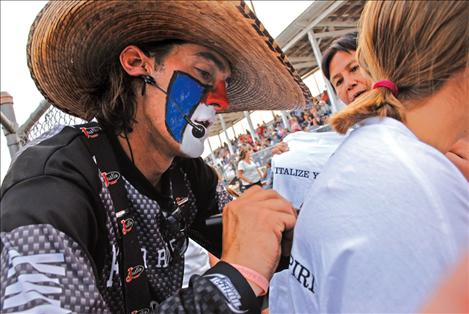 Rodeo clown Danger Dave autographs a young lady's T-shirt at the Thursday night performance of the Flathead River Rodeo, and Indian National Finals tour rodeo. Legend had it Dave Whitmoyer played  football for the Carroll College Saints and is a hunting guide when he's not performing at rodeos.