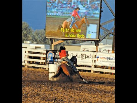 Faith Holyan can be seen in the jumbotron as she rounds a barrel.