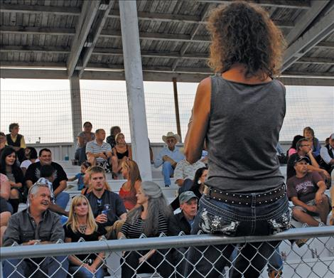 A spectator snaps a photo during the rodeo.