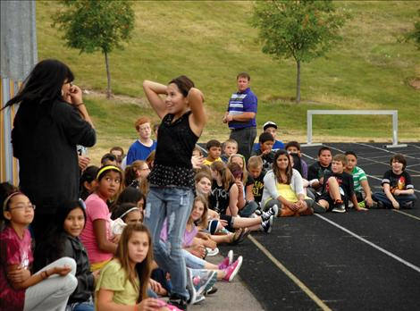Polson Middle School sixth graders sit on the track as they listen to speakers at the Graduation Matters kickoff.