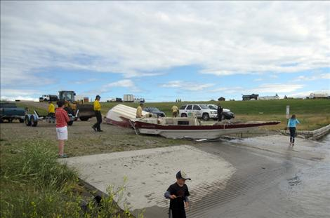 A boat is hauled out of the Flathead River after a storm sank it Tuesday night, Aug. 14.