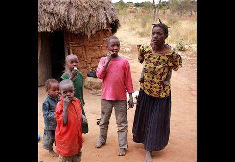 A young lady, not yet 30, with five children and no food is happy to see Jack Stivers and Meshack Itumo with food. The home is made from mud bricks.