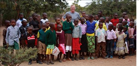 Kenyan children stand with Jack Stivers in front the orphanage. Clothes and shoes are constant needs, as well as medical care and glasses.