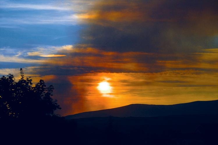 Smoke from the West Garcon fire spills over the foothills into the Polson area on the evening of Monday, Aug. 13.