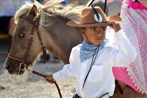 Little cowboy Abul Learn, 5, leads a horse around the entire parade course with his sister, Eve, 9, riding along.