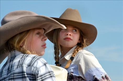 Sisters Coral, left, and Yzabel Mergenthaler rode on the Idle Spur float, fashioned by their grandfather.