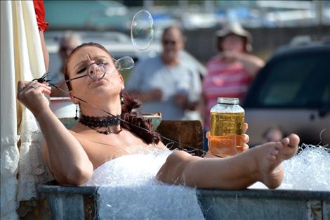 Dance Hall Girl Rachel Schreiner rides in an old bathtub on the prize-winning float, unSoiled Dove.