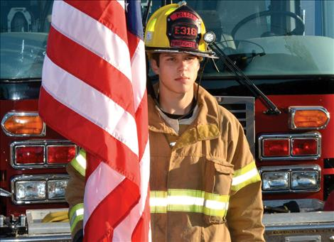 "Junior firefighter Taylor Haynes, 16, stands for the fallen of 9/11. He said he remembers the day, ""a lttle bit."""