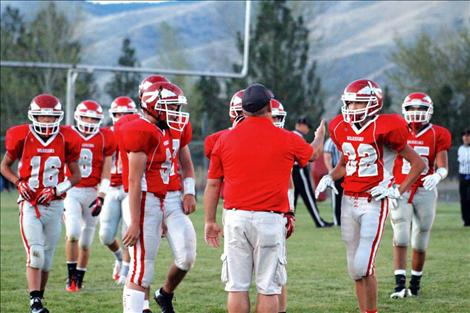The Arlee Warrior football team gathers around for instruction during their homecoming game against Drummond. Head coach Mike Rogers doesn't let the inexperience of his young team daunt him, but continually encourages them as they improve.